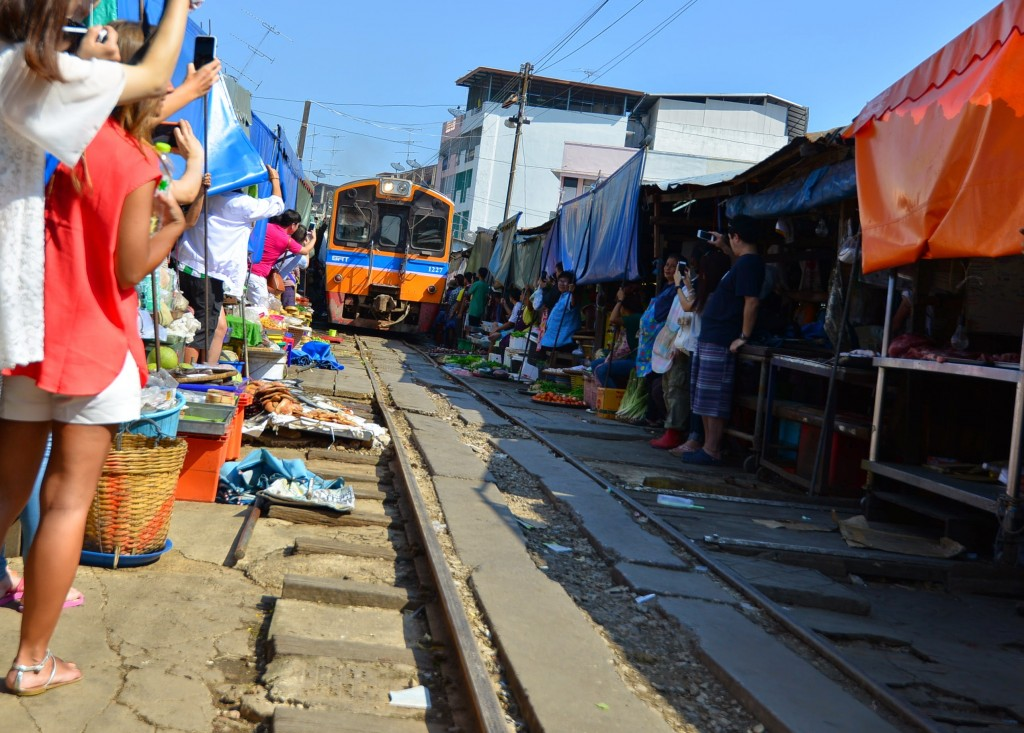 Train crawling through Maeklong Railway Market... ...the awnings and baskets are pulled back from the track just about enough distance so there is no contact with the train. And once the train passes, everything's back!